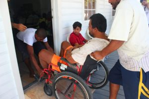 Man in a wheel chair helped into a house