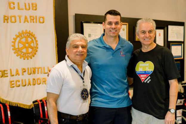 a picture of three people with an Ecuador banner in the background
