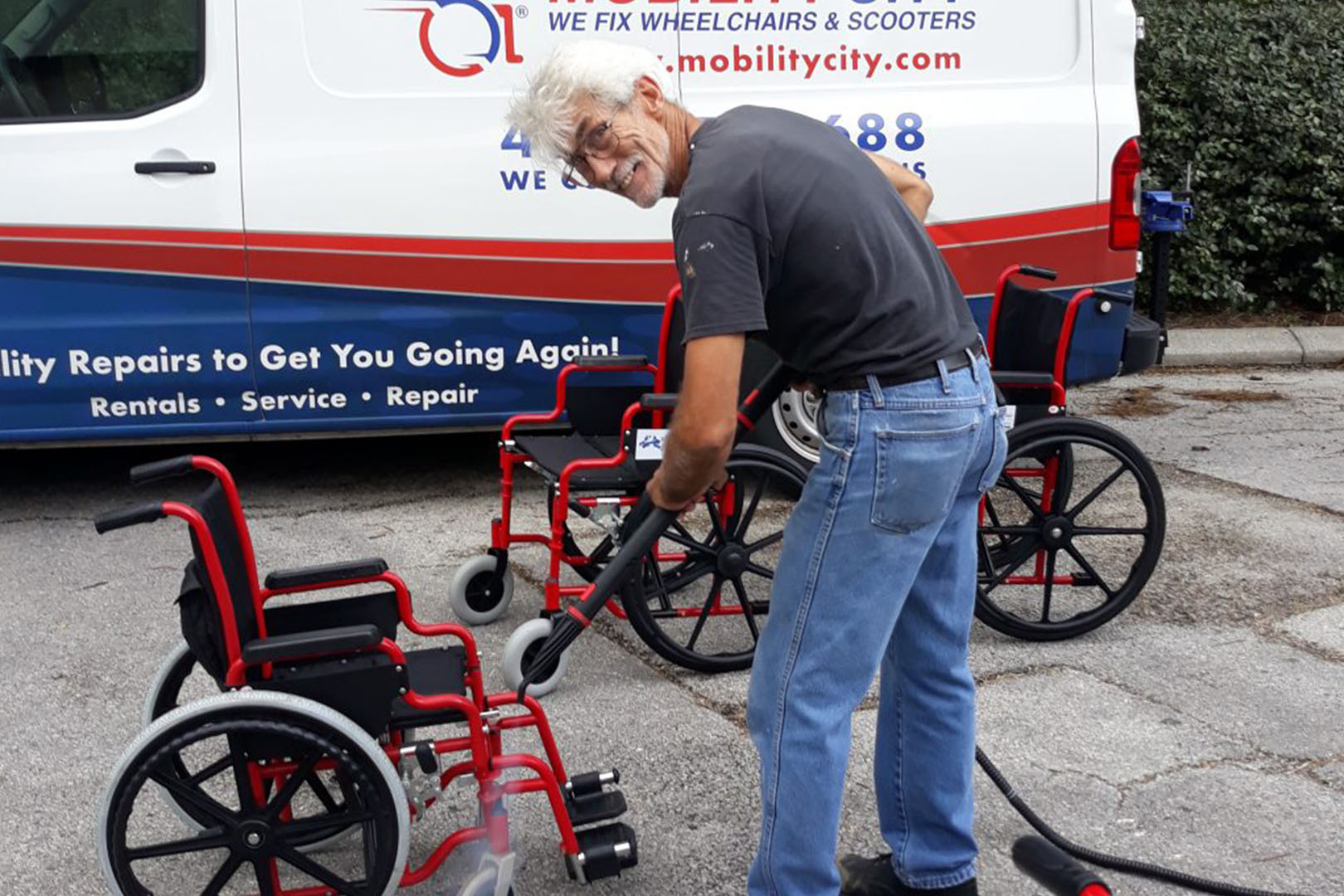 Volunteer cleaning a wheelchair