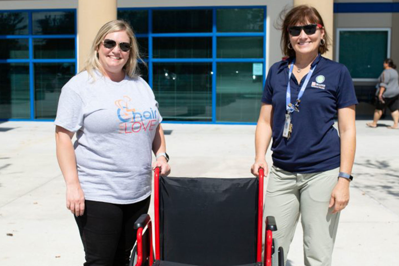 Two women posing with a wheelchair between them