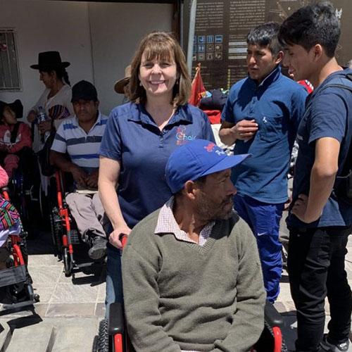 Barbara Welch pushing a man in a wheelchair