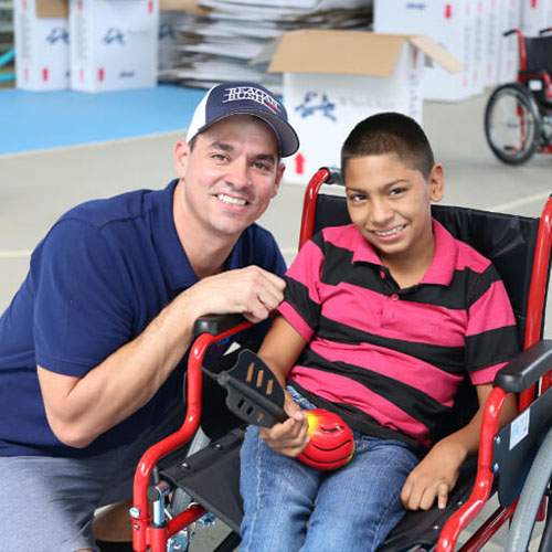 Jason Debono crouched next to a boy in a wheelchair