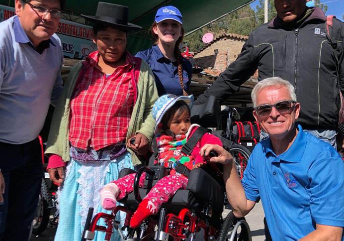 volunteers with the family of a little girl who just got a wheelchair