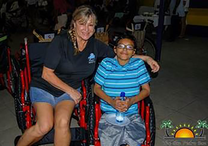 A volunteer sitting with a kid in a wheelchair