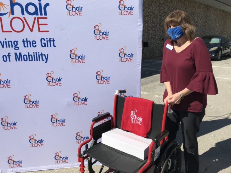 Woman standing with a new wheelchair for OCPS in front of a Chair the Love backdrop